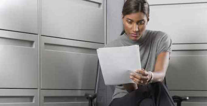Businesswoman reading paperwork